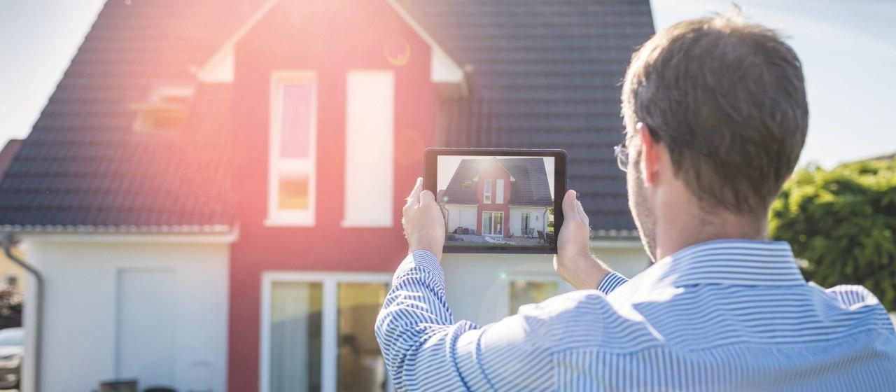 Makler der ein Haus mit einem Tablet fotografiert