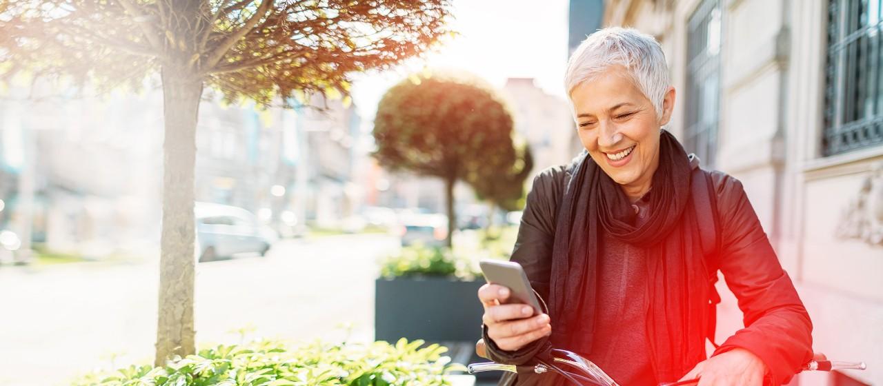 Grauhaarige Frau mit Smartphone