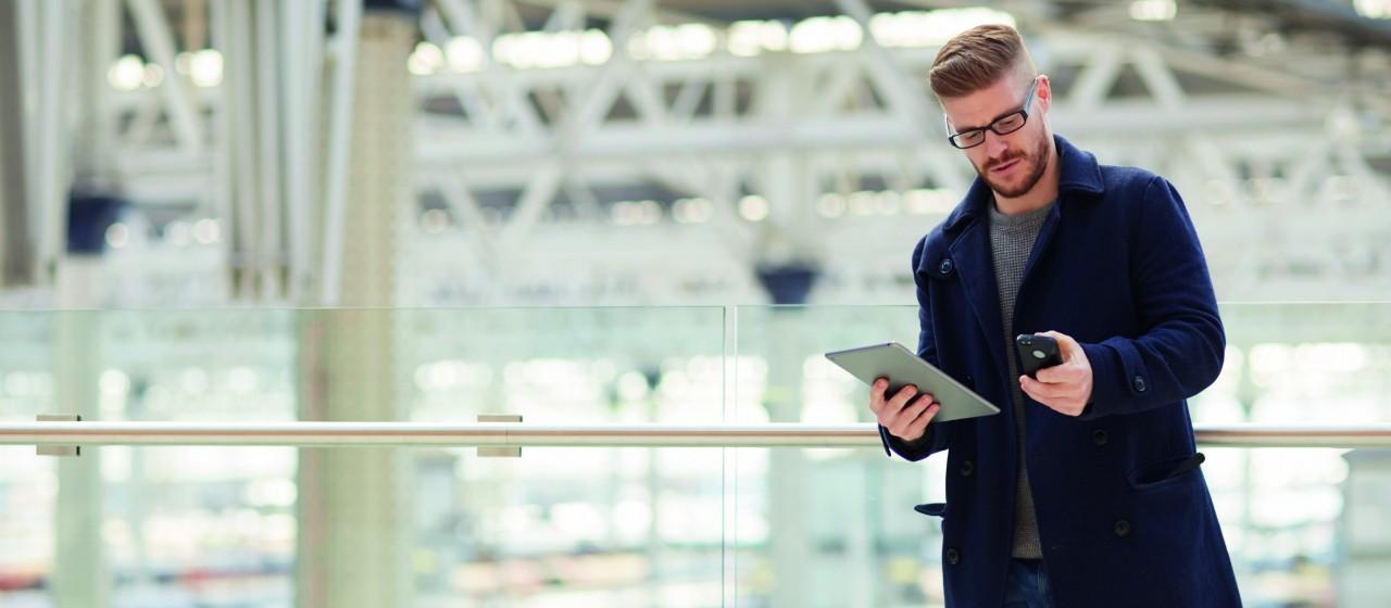 Mann mit Smartphone und Tablet Computer in der Hand