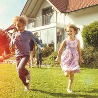 Kinder die im Garten hinterm neuen Haus spielen