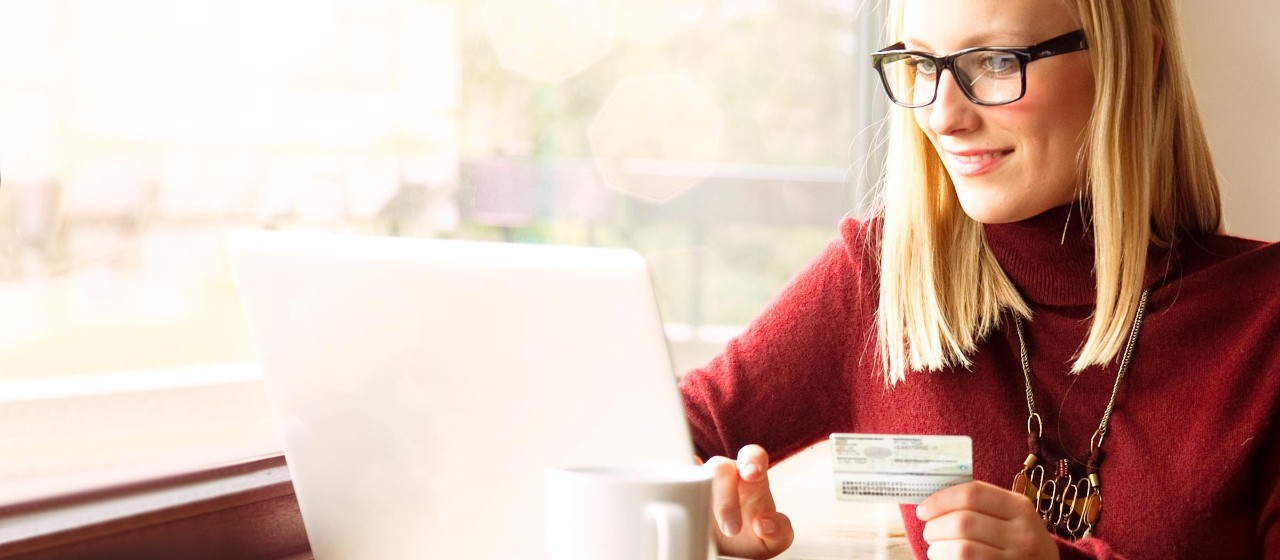 Frau mit Personalausweis vorm Laptop